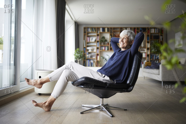 Happy senior woman with hands behind head sitting on chair at home