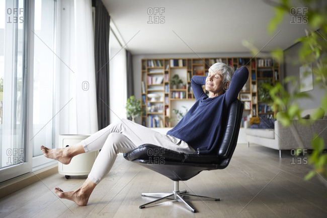 Contemplating senior woman with hands behind head sitting on chair at home
