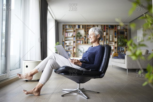 Active senior woman using laptop while sitting on chair at home