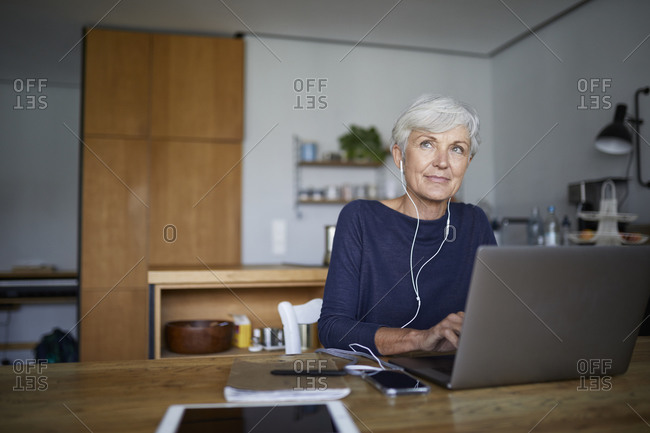 Senior woman working on laptop while sitting at home