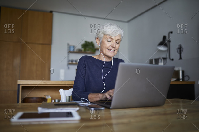 Active senior working on laptop while listening music sitting at home