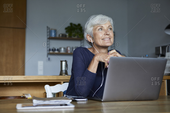 Active senior woman listening to music from smart phone at home