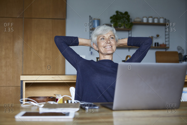 Smiling senior woman with hands behind head relaxing while sitting at home