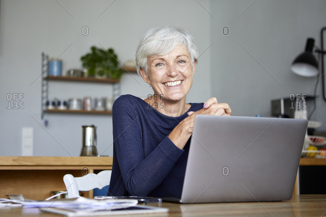Smiling active senior using laptop while sitting at home
