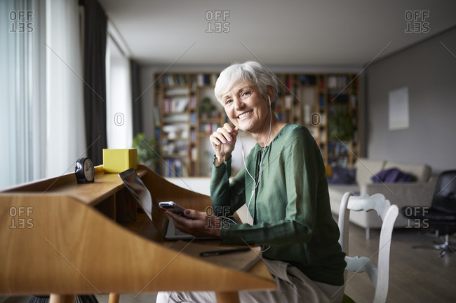 Smiling active senior woman listening music while sitting on chair at home