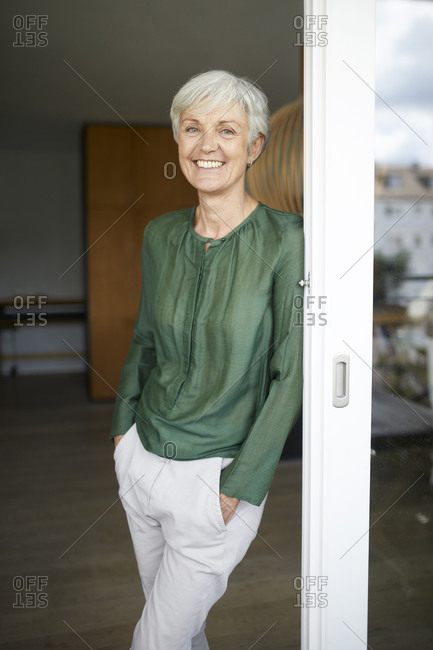 Smiling woman leaning on window with hands in pockets