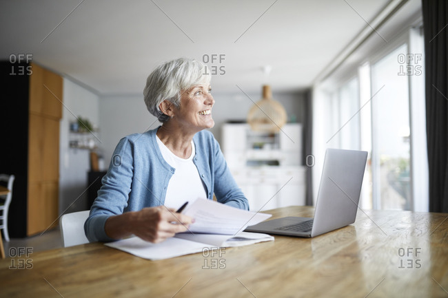 Active senior woman doing paper work while sitting at home