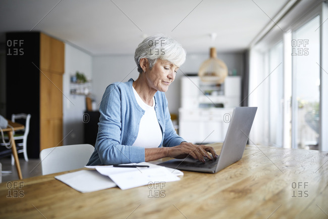 Senior woman working on laptop while sitting on chair at home