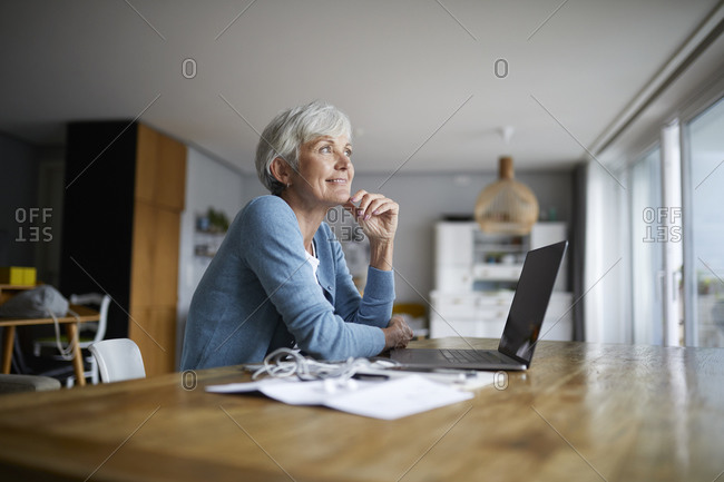 Contemplation senior woman with hand on chin sitting at home