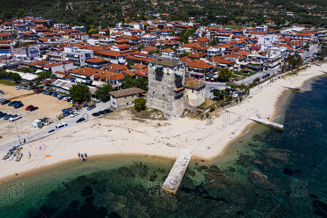 Greece- Chalkidiki- Ouranoupoli- Aerial view of beach and old tower at edge of coastal village in summer