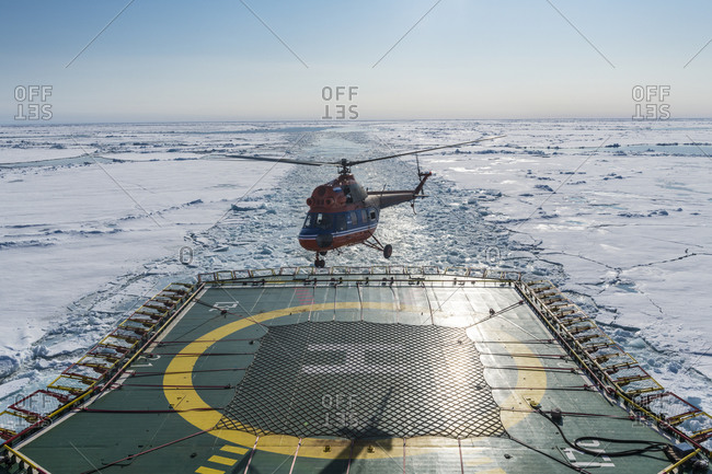 Helicopter landing on helipad of ice-breaker 50 Years of Victory cleaving through ice of Arctic Ocean