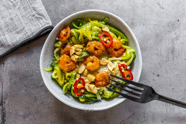 Close-up of zoodles with shrimps and chili served in bowl on table