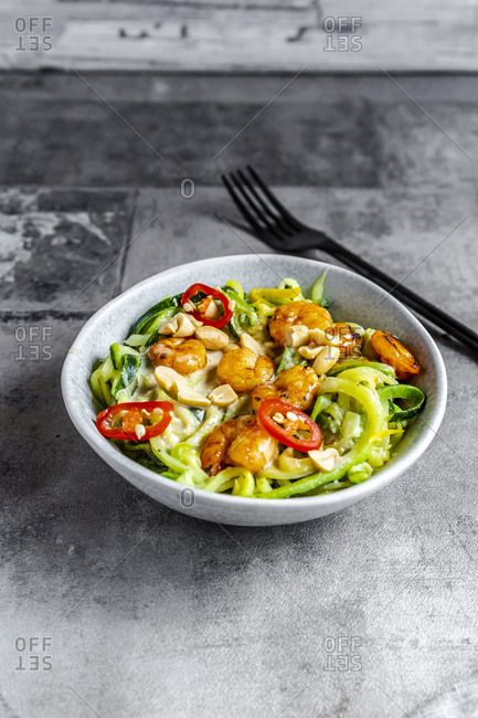 Close-up of zoodles with shrimps and chili in bowl served on table