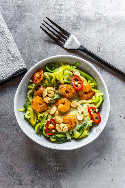 Zoodles with shrimps and chili served in bowl on table