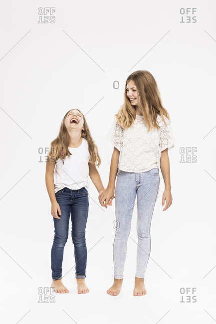 Cheerful sisters holding hands while standing against white background