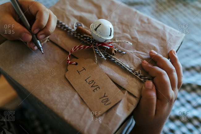 Hands of boy writing on Christmas present at home