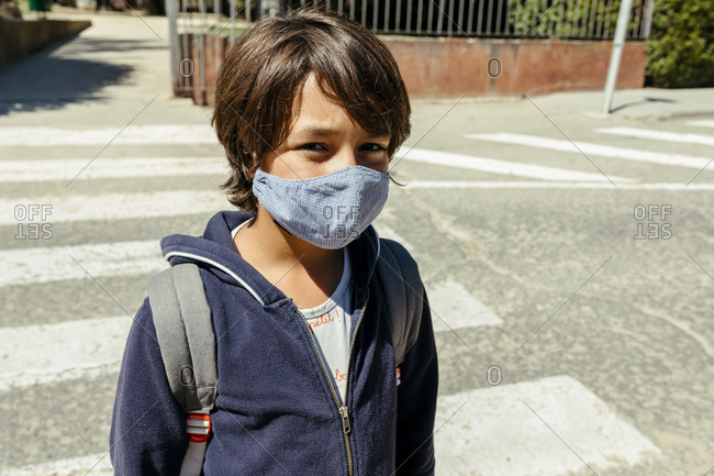Schoolboy wearing mask standing on road during sunny day