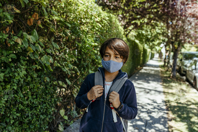 Schoolboy wearing mask looking away while standing by plants on footpath