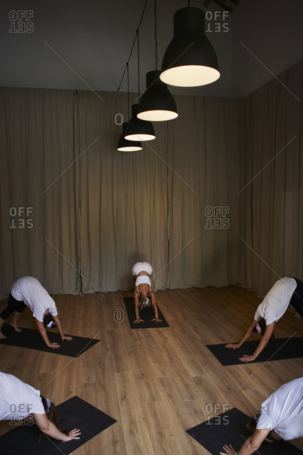 Yoga instructor with women practicing downward facing dog position in studio