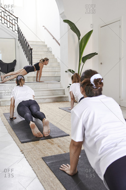 Yoga instructor with women practicing plank position in health club