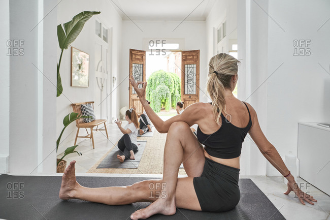 Female instructor guiding women in exercising at yoga studio
