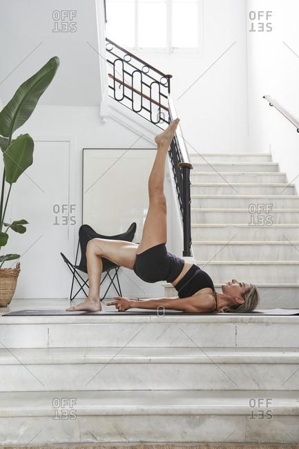 Mature woman practicing one-legged bridge pose in yoga studio