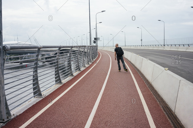 Young man with backpack inline skating on bridge against sky in city