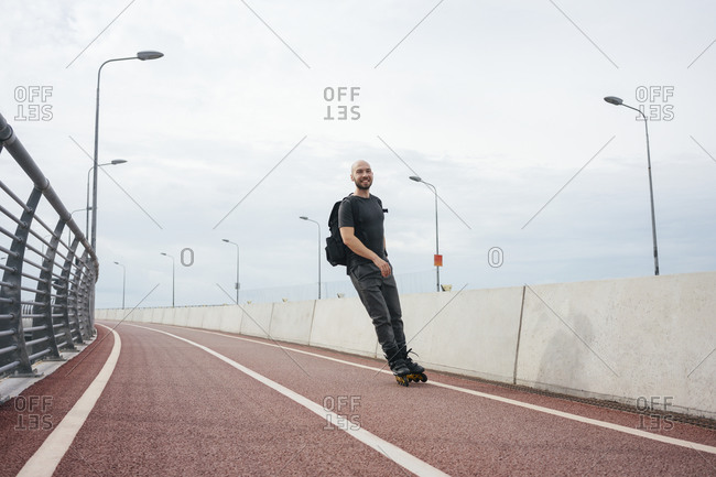 Young man inline skating on bridge against cloudy sky in city