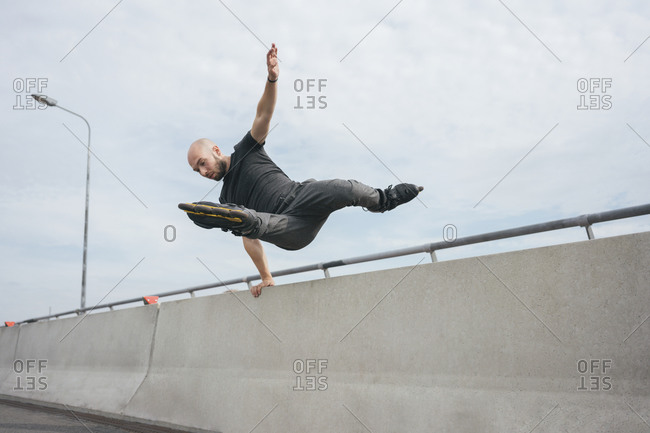 Carefree young man with inline skates jumping over railing on bridge