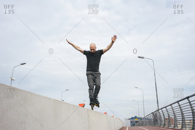 Young man with arms raised inline skating on railing against cloudy sky