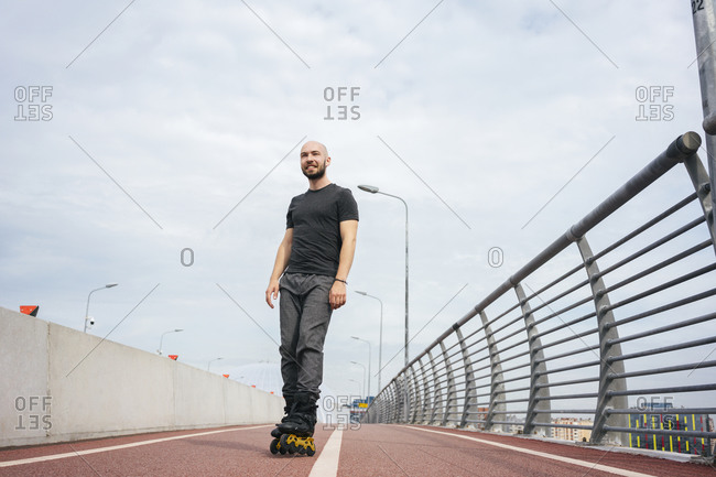 Smiling young man looking away while inline skating on bridge against cloudy sky