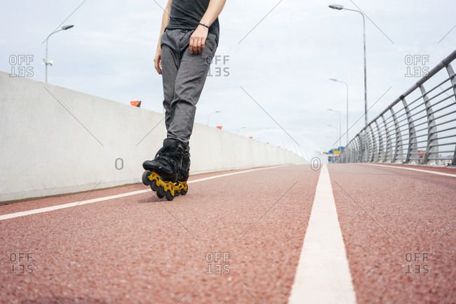 Legs of young man inline skating on bridge against sky in city