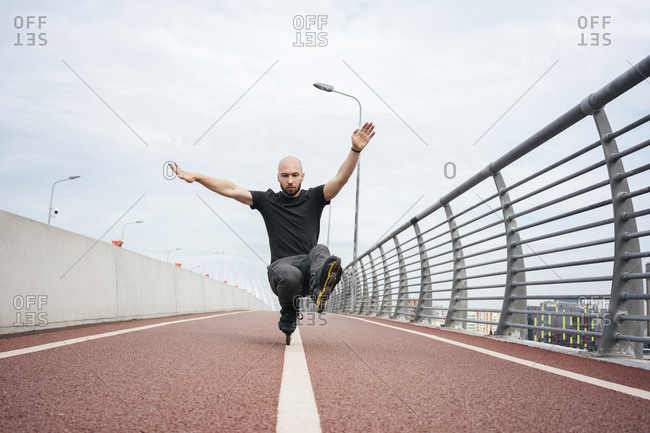 Young man performing stunt while inline skating on bridge against sky