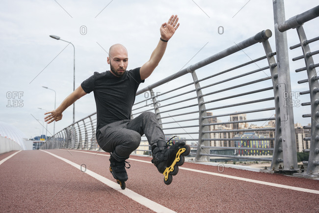 Young man inline skating while crouching on bridge against sky