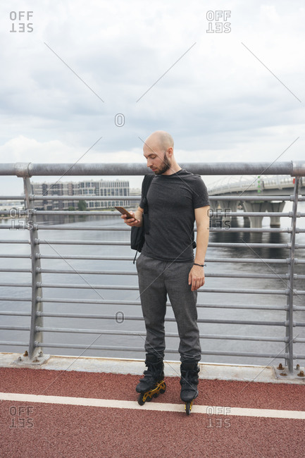 Young man with inline skates using smart phone while standing on bridge against sky