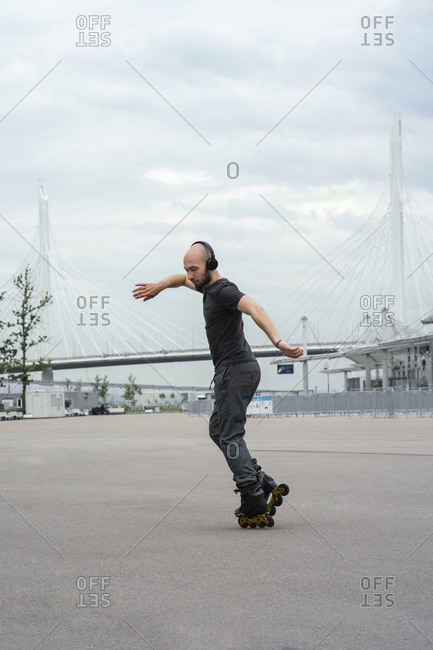 Man listening music while inline skating on road against cloudy sky