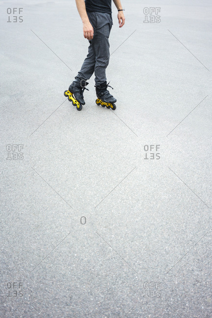 Legs of young man inline skating on road