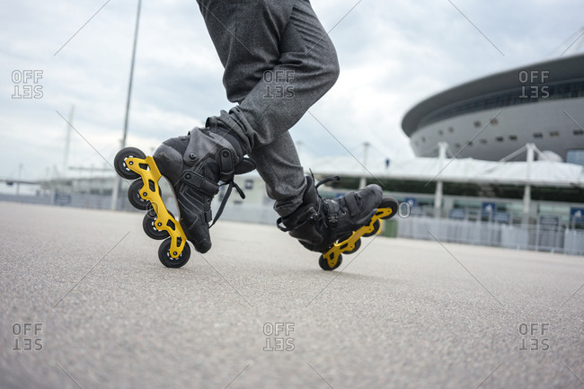 Legs of young man inline skating on road against sky