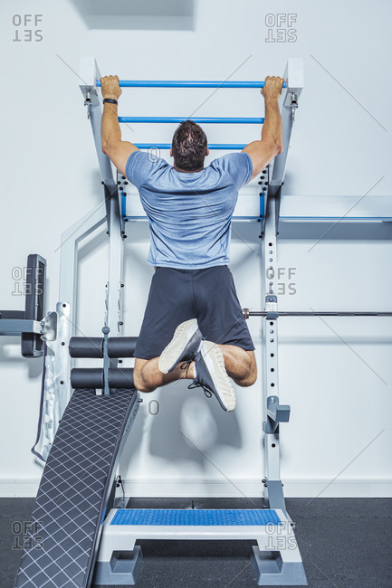 Male athlete exercising on chin-ups bars in gym