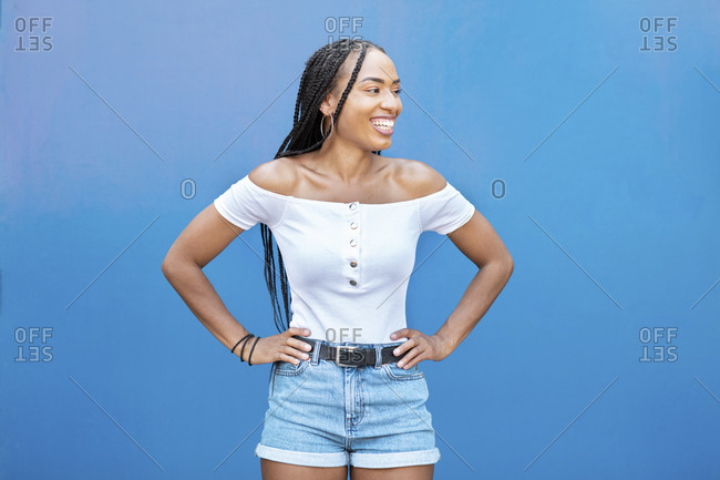 Smiling woman with hand on hip standing against blue wall
