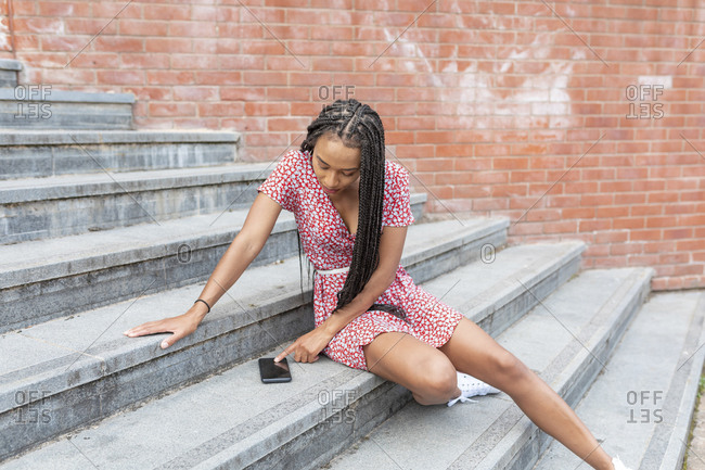 Young woman using mobile phone while sitting on staircase in city