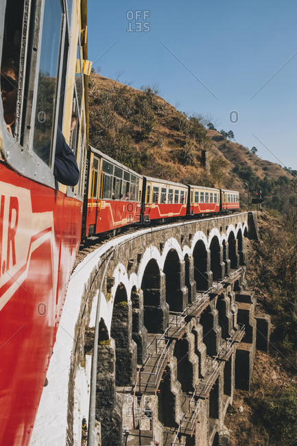 Shimla, India -  January 20, 2018: Train passing through an arched bridge in the countryside, from Kalka to Shimla.