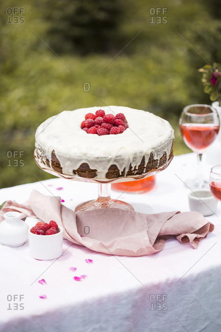 Carrot cake with raspberries on an outdoor table