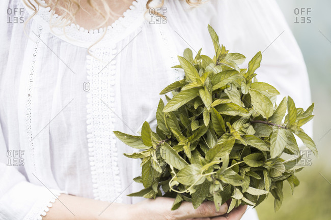 Close up of a woman in a white dress holding a bunch of mint