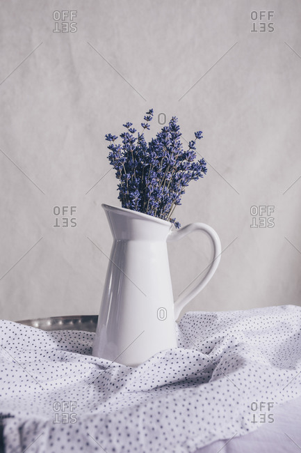 Lavender in a white vase on a table with linen