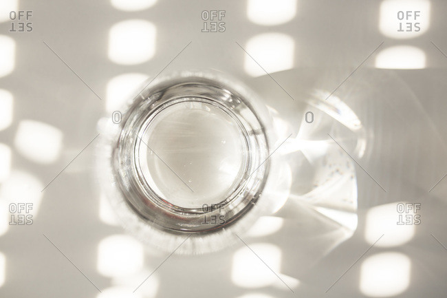 Overhead view of an empty glass on a white table