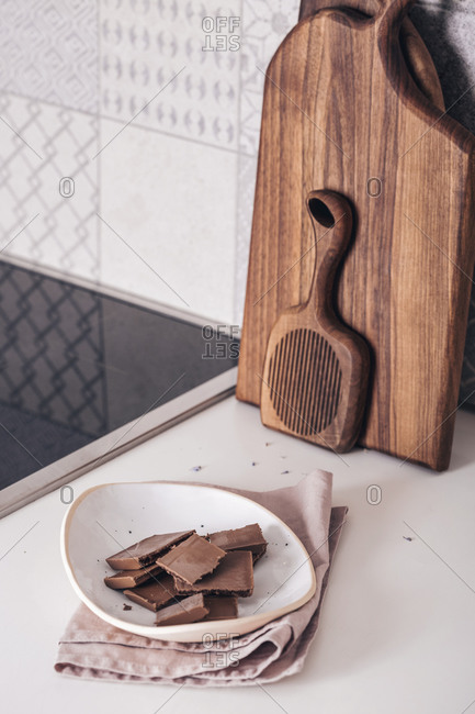 Chocolate pieces on a plate on the kitchen counter with wooden boards