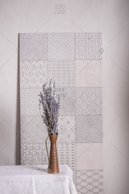 Lavender in a vase on a table with tile pattern background