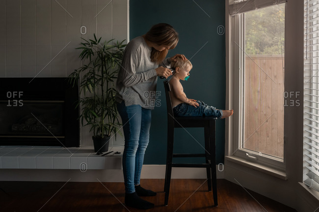 Mother giving toddler boy an at home haircut