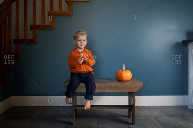 Adorable little boy sitting on bench beside a pumpkin eating an apple